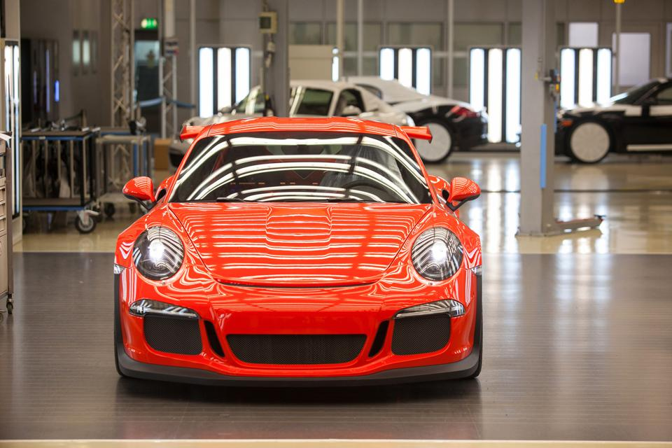 A red Porsche 911 GT3 RS automobile stands illuminated under strip lights ahead of shipping from the Porsche AG factory in Stuttgart, Germany. Photographer: Krisztian Bocsi/Bloomberg