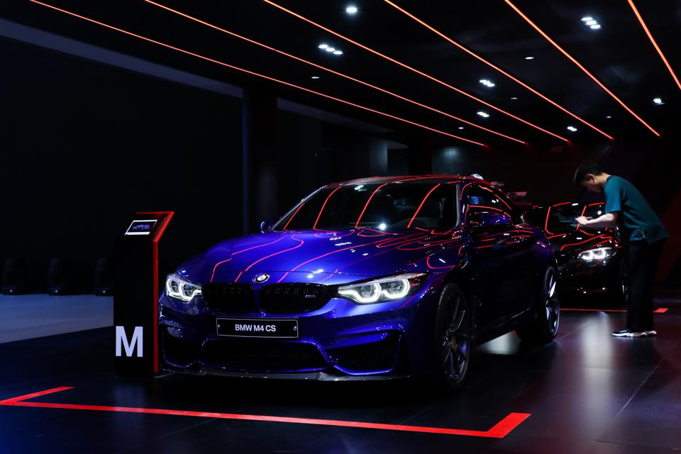 An attendee takes a photograph of a BMW M4 CS vehicle on display during the press day of the 2018 Busan International Motor Show. Photographer: SeongJoon Cho/Bloomberg