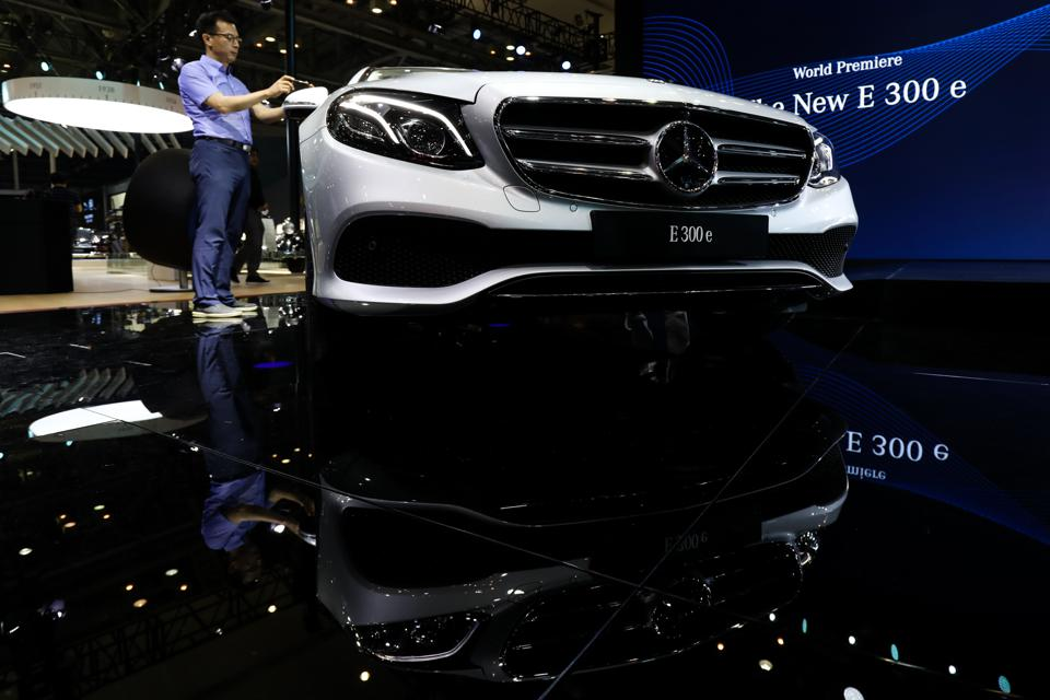 An attendee takes a photograph of a Mercedes-Benz AG E300e during the press day of the 2018 Busan International Motor Show in Busan, South Korea Photographer: SeongJoon Cho/Bloomberg