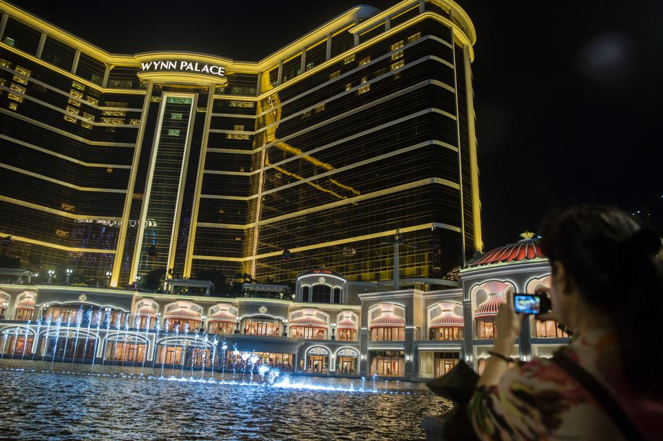 A guest (R) takes a photo of where the light, water and sound show is put on at Performance Lake in front of the Wynn Palace casino in Macau on August 22, 2016. / AFP / ISAAC LAWRENCE (Photo credit should read ISAAC LAWRENCE/AFP/Getty Images)