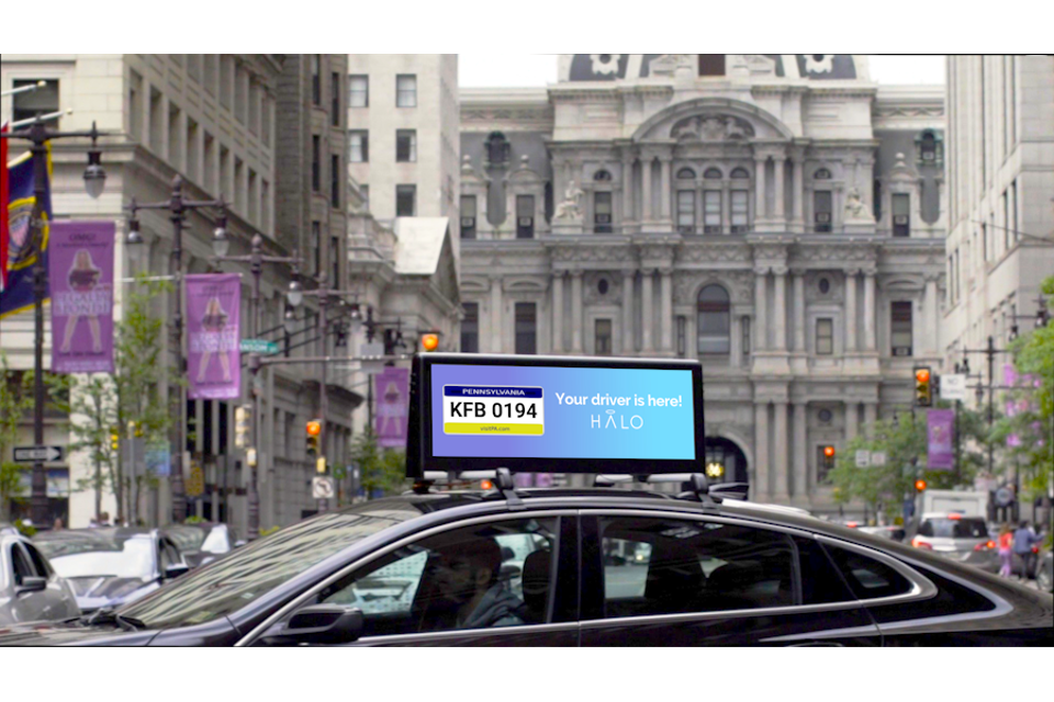 A ride-share driver displays the vehicle's license plate on Halo Car's roof-mounted mobile ad display screen.