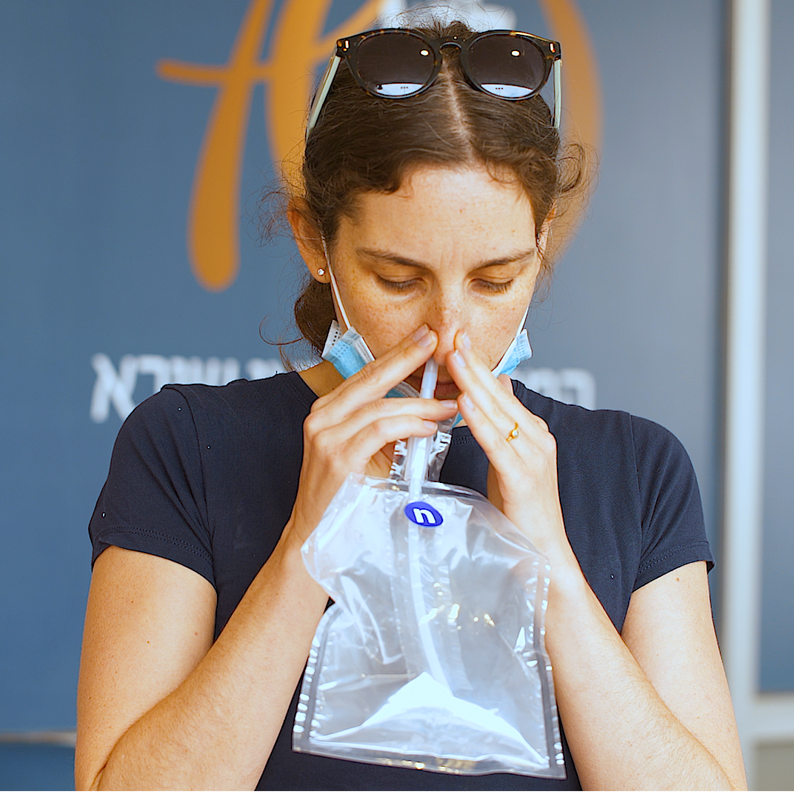 Female volunteer breathing into NanoScent's Scent Check device to test for Covid-19.