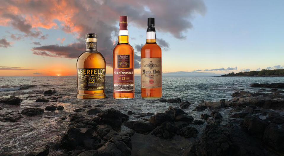 Three bottles of scotch with a sunset backdrop overlooking Maui, Hawaii