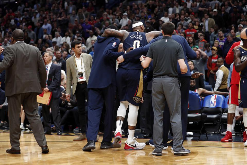 New Orleans Pelicans center DeMarcus Cousins is helped off the court after injuring his left Achilles tendon.