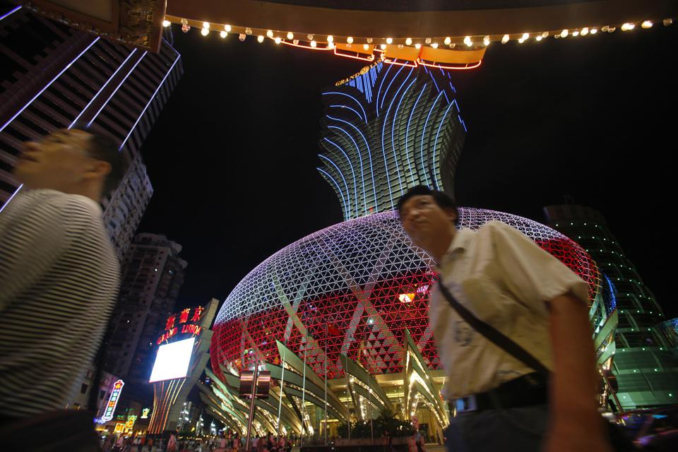 Visitors walk past Casino Grand Lisboa in Macau Saturday, July 25, 2009. Macau chooses its first new leader Sunday since returning to Chinese rule a decade ago. But there's no doubt about who the next chief executive will be: The former culture minister Fernando Chui is the only candidate. (AP Photo/Vincent Yu)