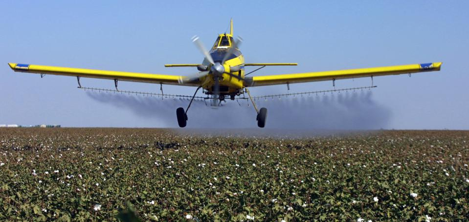 Pesticides plane sprays over crops.