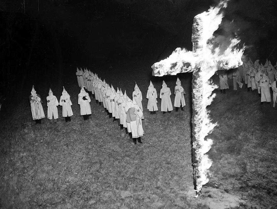 Members of the Ku Klux Klan, wearing traditional white hoods and robes, watch the burning a 15-foot cross at Tampa, Fla.
