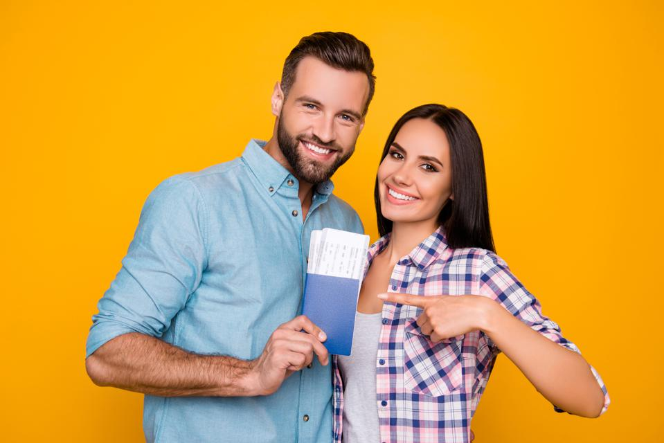 Portrait of joyful glad couple holding passport with flying tickets in hands pointing with forefinger looking at camera isolated on bright yellow background
