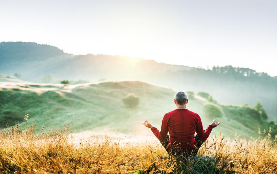 Senior man meditating outdoors in nature in the foggy morning at sunrise. Copy space.