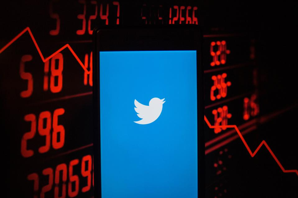 A smartphone displays the Twitter application with a