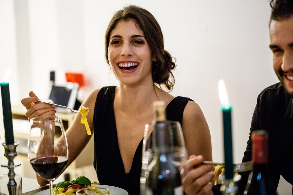 Woman having pasta during dinner party at home