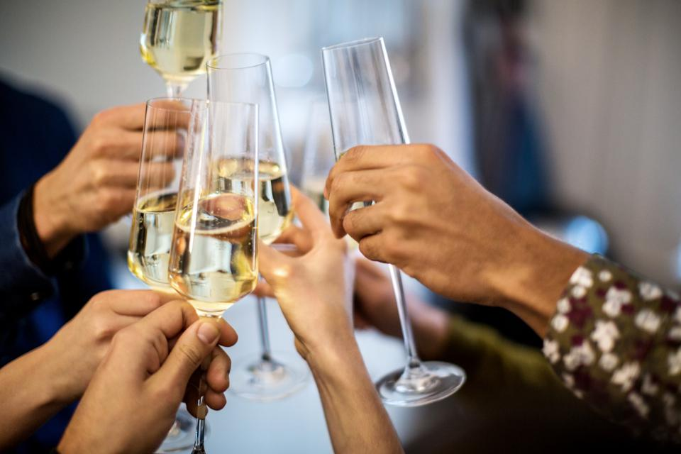 Hands toasting champagne flutes during dinner party