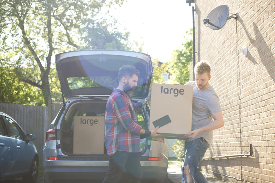 Male gay couple unloading moving boxes from car