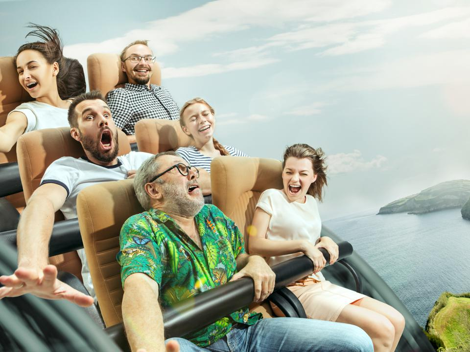The happy emotions of men and women having good time on a roller coaster in the park