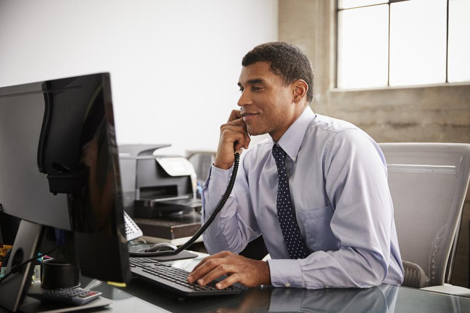 Businessman at an office desk using phone and computer