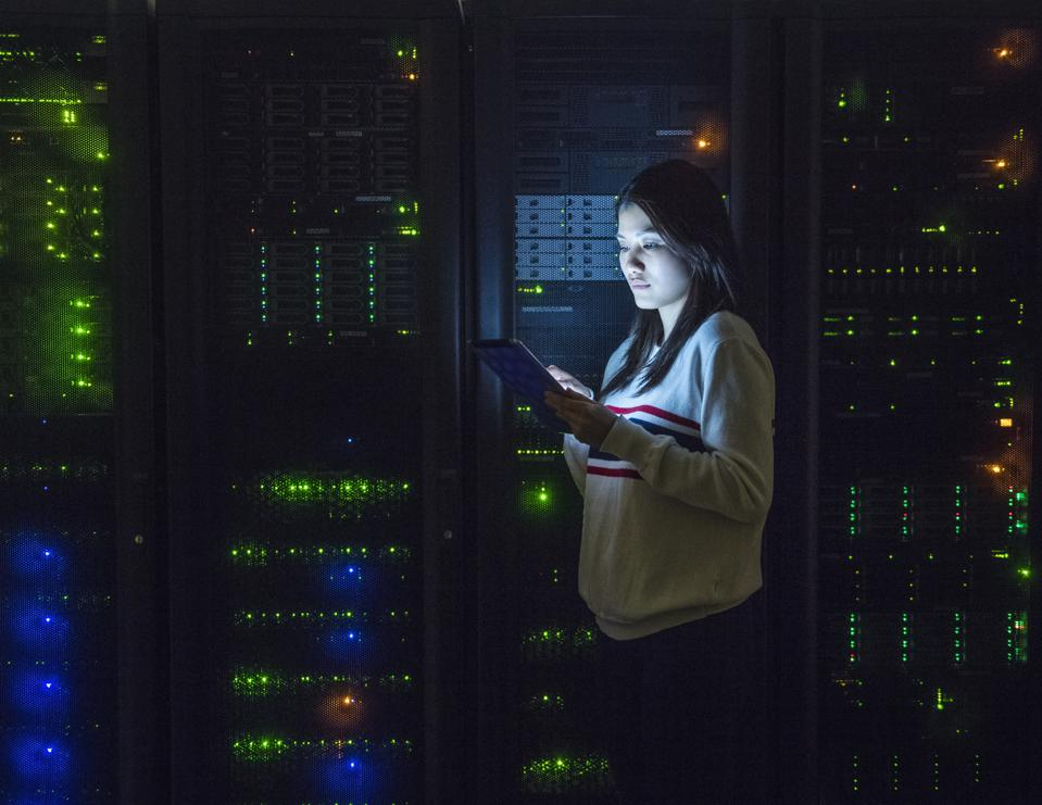 Young woman working on digital tablet in server room