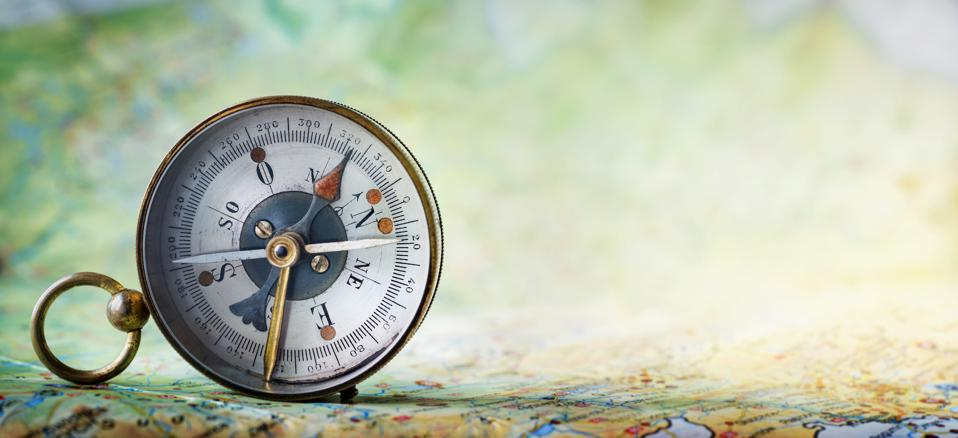 Magnetic old compass on world map.