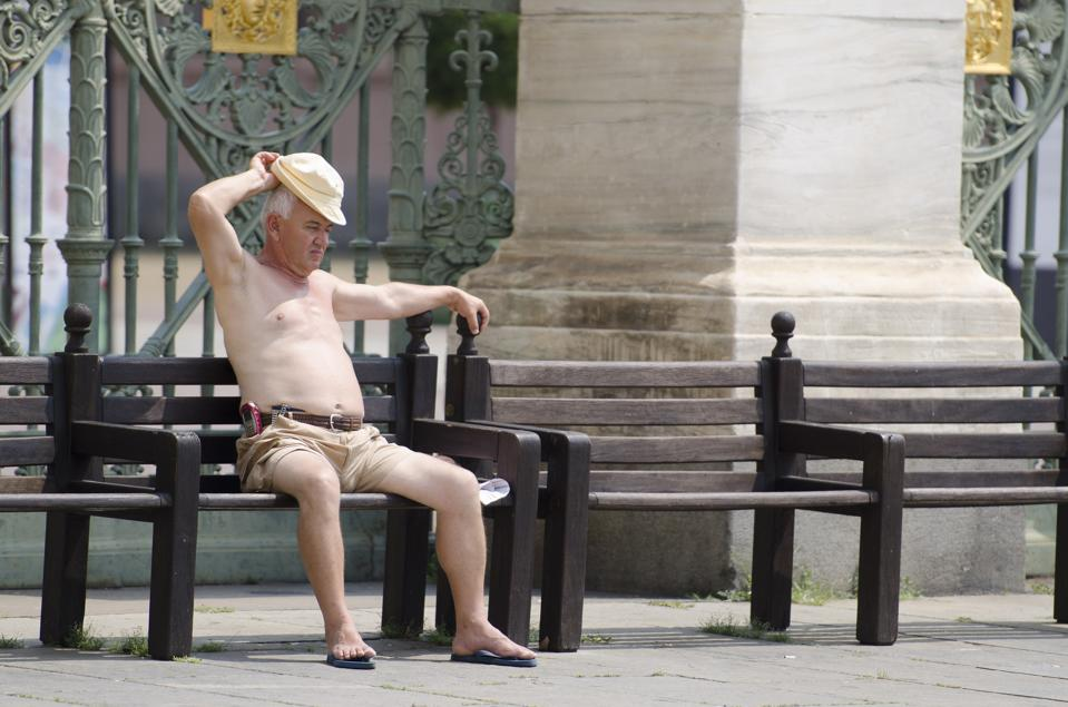An elderly man is enjoying the sun with the naked chest on a...