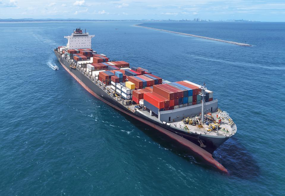 Aerial view of cargo ship runing on sea close warehouse harbor at thailand .