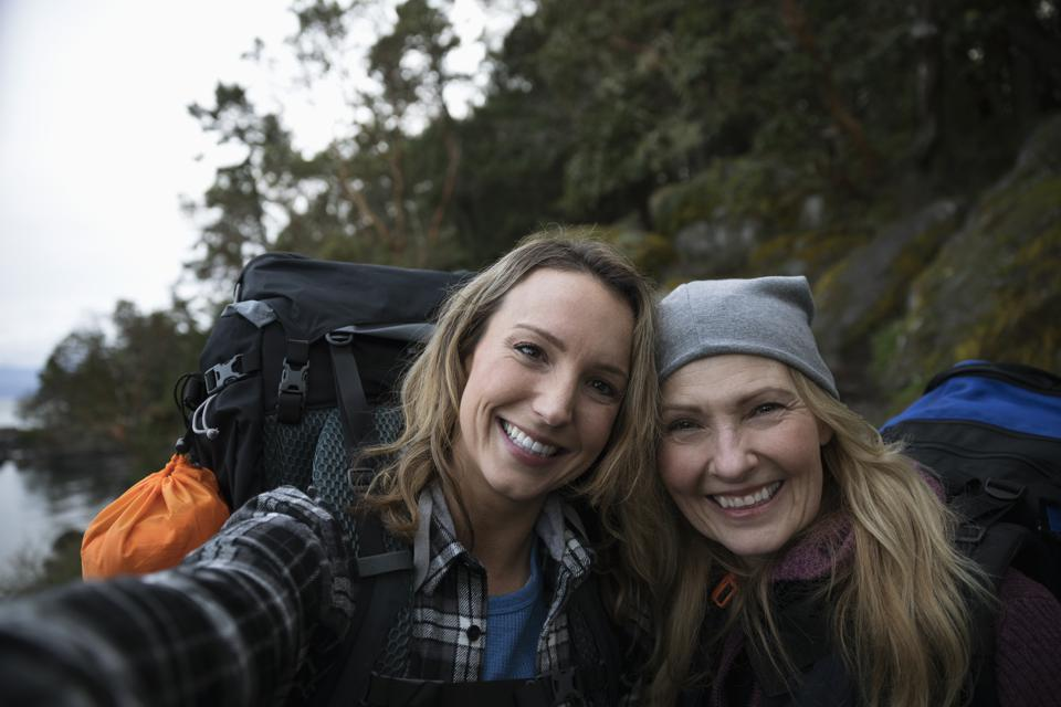 Portrait happy mother and daughter backpacking, taking selfie