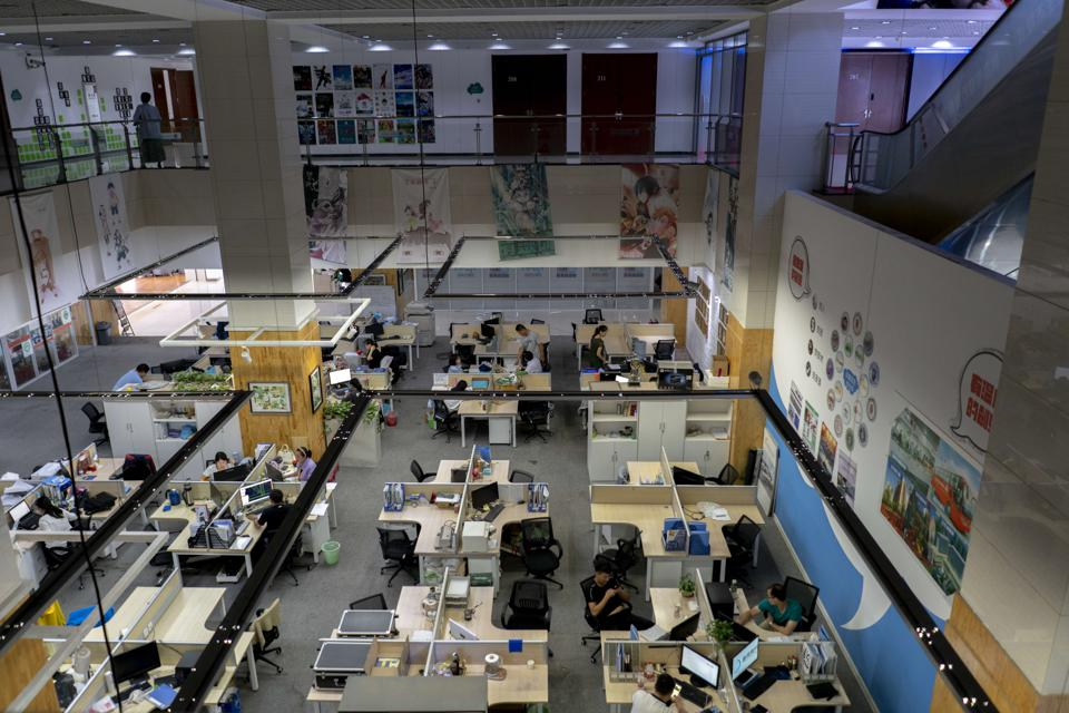 Young people are working in an open office space, which is a...