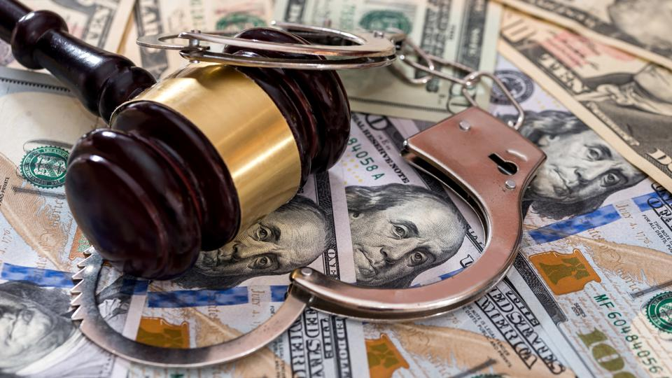 Steel handcuffs with judge's gavel on dollar banknotes