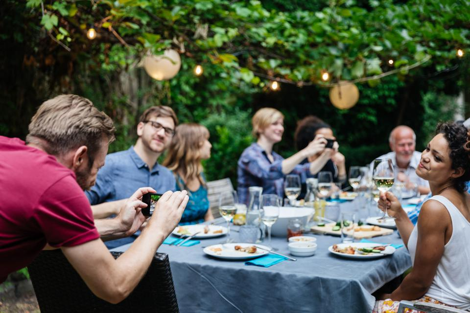 Man Taking Photo Of Friends At Family BBQ