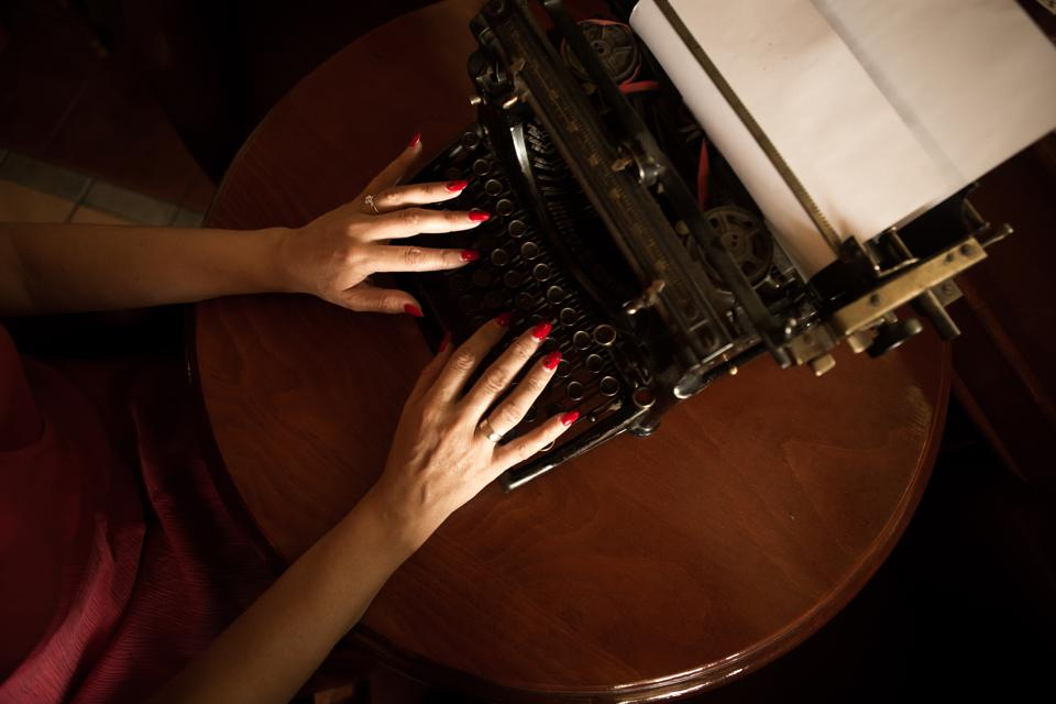 Look at the hands of a writer who writes on an old typewriter