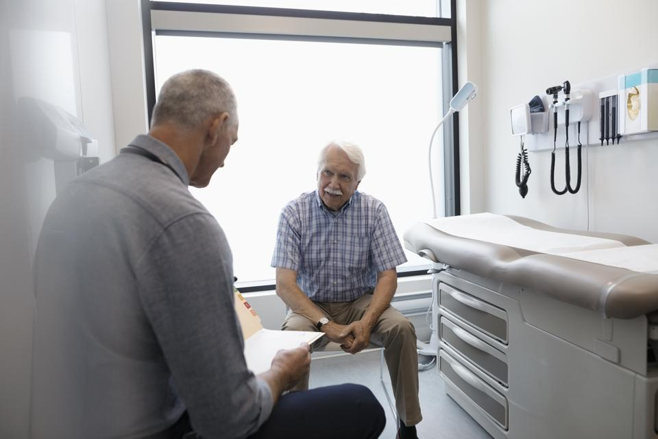 Male doctor discussing medical record with senior patient in clinic exam room