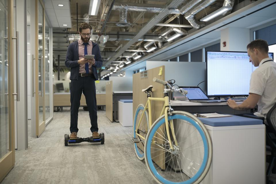 Creative businessman with digital tablet on hoverboard in office