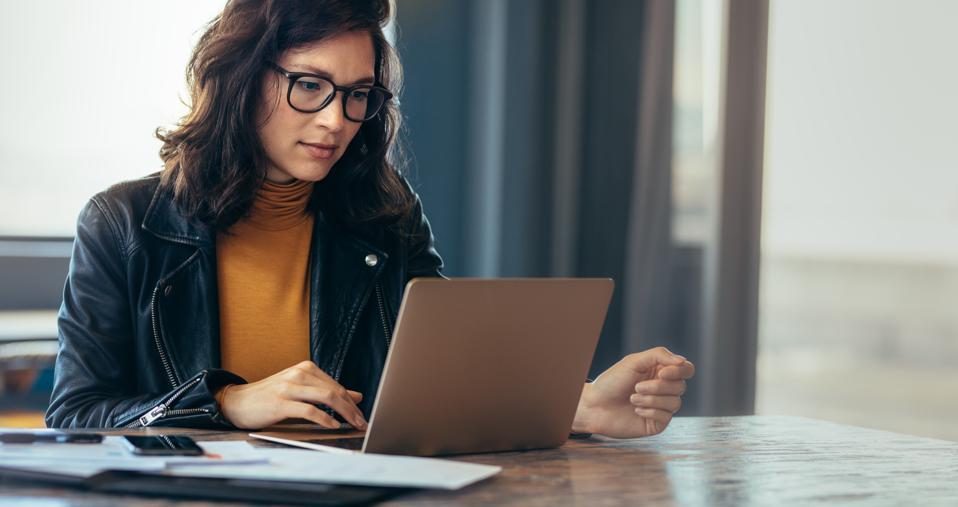 Nainen työskentelee kannettavan tietokoneella toimistossa