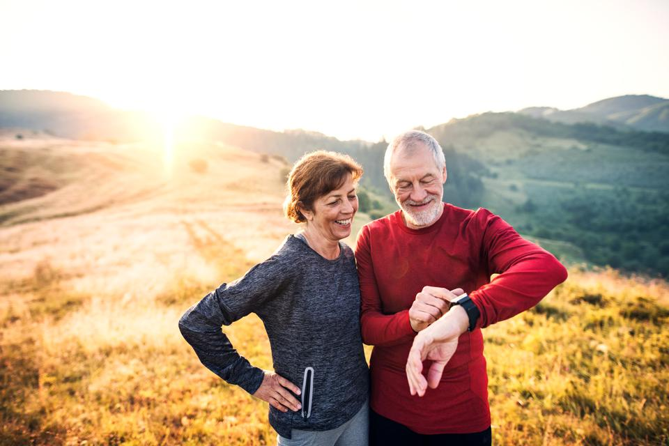 Senior couple runners resting outdoors in nature at sunrise, using smart watch.