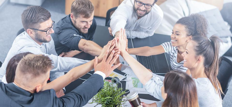 Happy business people team giving high five in office.