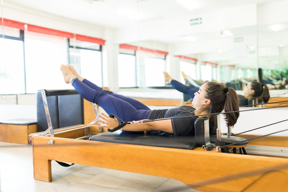 Determined Woman Pulling Resistance Bands On Pilates Reformer