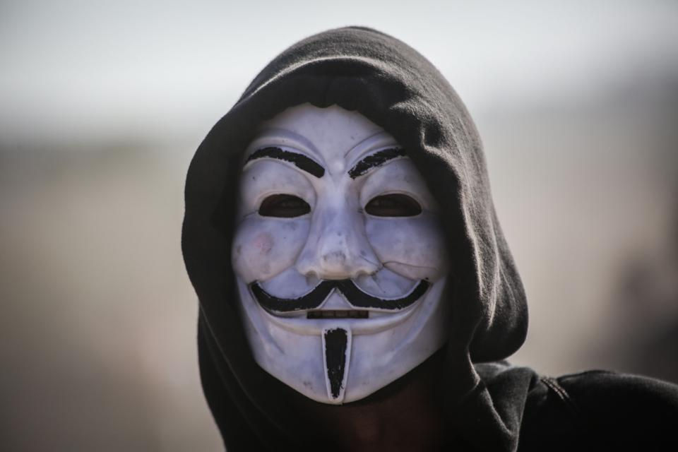 A man in a black hoodie wearing an Anonymous mask