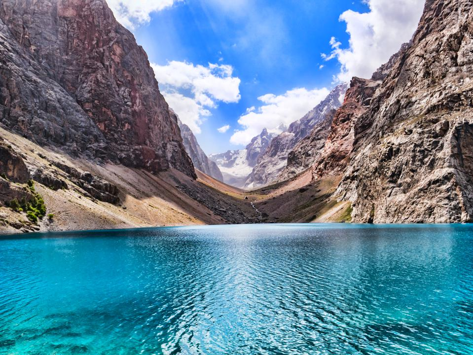 Big Alo mountain lake with turquoise water in sunshine on rocky mountain background. The Fann Mountains, Tajikistan, Central Asia