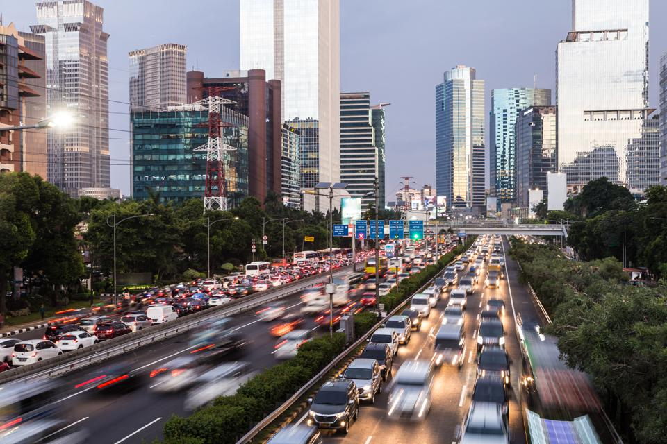 Rush hour traffic captured with blurred motion along the Gatot Subroto highway in the heart of Jakarta business district in Indonesia capital city at dusk