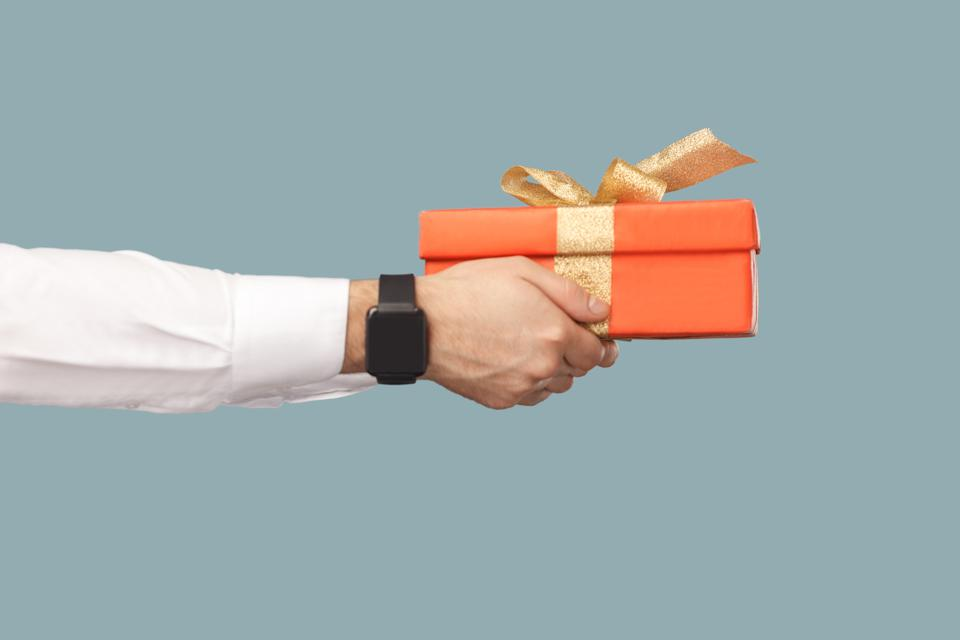 Business people concept, richly and success. human hand in white shirt with black smart watches holding red gift box with gold ribbon.