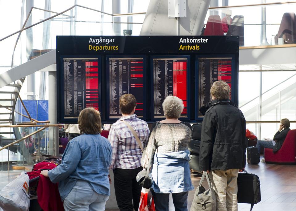 Travelers looking at passenger information screens at Stockholm Arlanda Airport in Sweden.