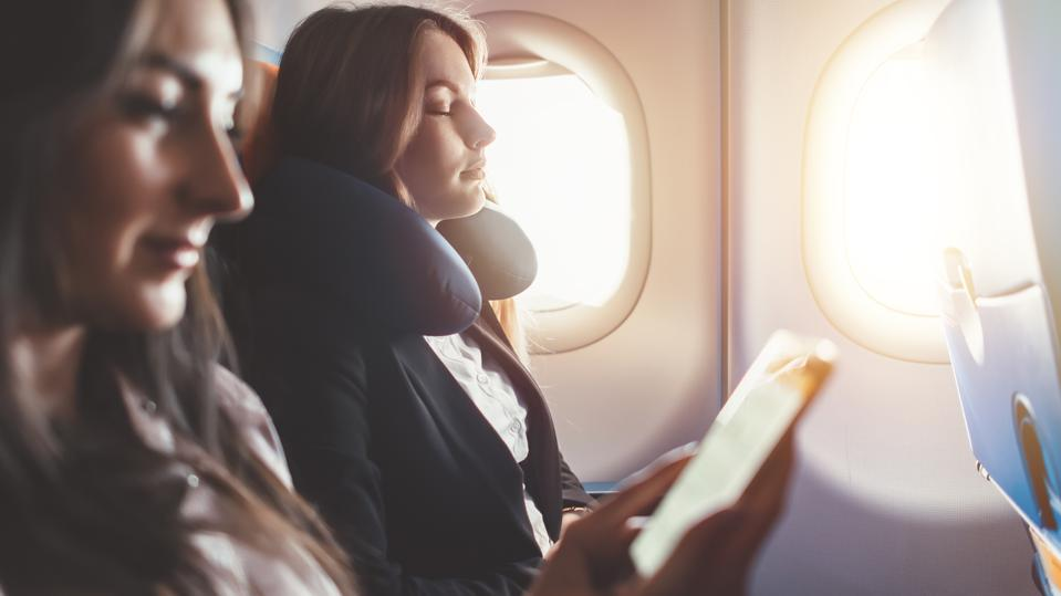 Two females going on business trip by plane. A woman reading an e-book on a smartphone