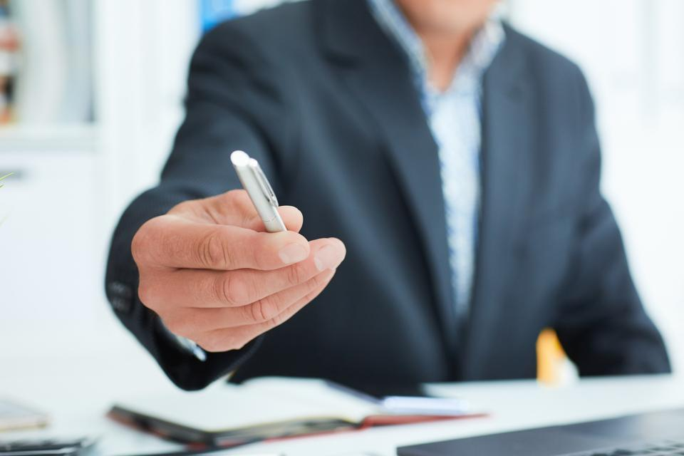Male arm in suit offer silver pen to sign contract closeup. Strike a bargain for profit, white collar motivation, union decision, corporate sale, insurance agent concept