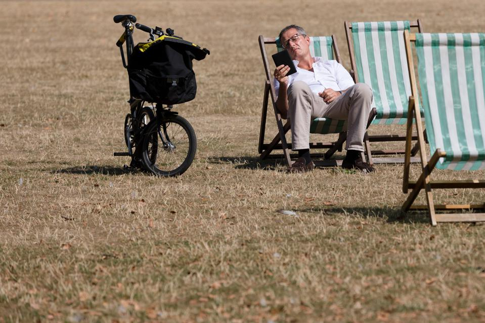 Man Sitting In A Deckchair With a Brompton Bicycle
