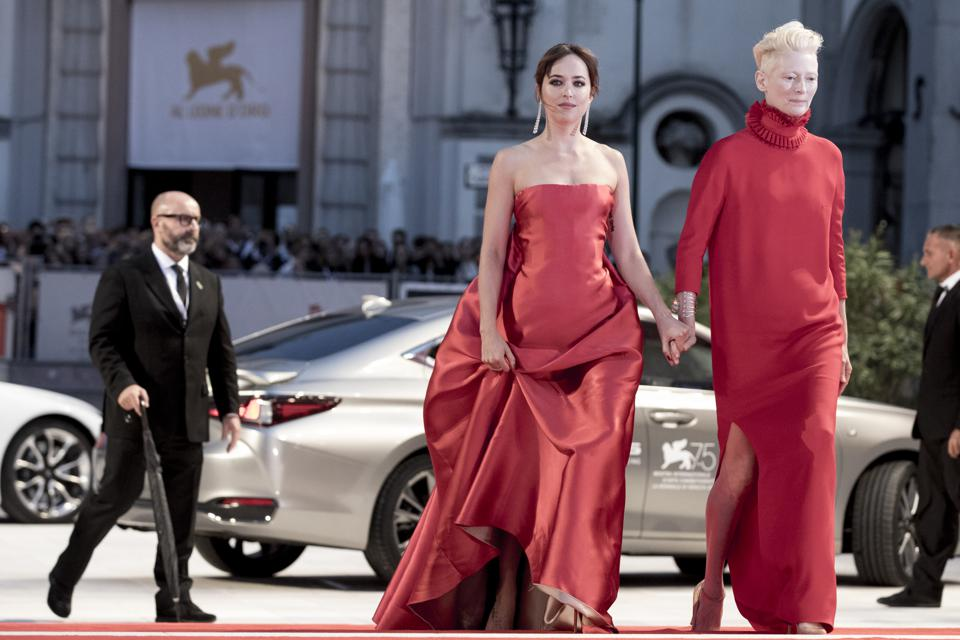 Red Alert: Dakota Johnson (in a Dior Couture gown) and Tilda Swinton (in Haider Ackermann) walk the matching carpet at the premiere of 'Suspiria' in Venice.