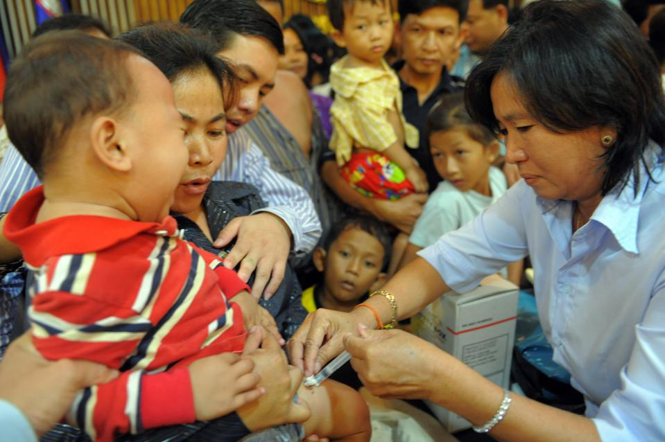 A child receives a vaccination from a health worker  in Cambodia