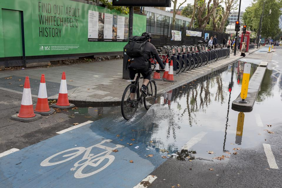 A cyclist rides through collected water on a bike lane in London.