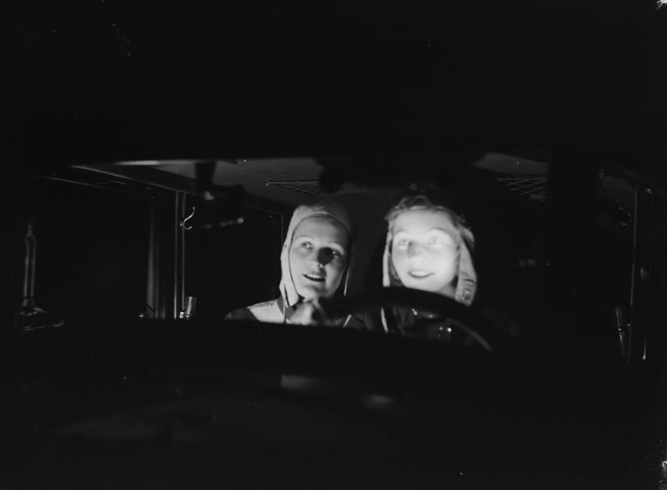 Two women in a car at night.