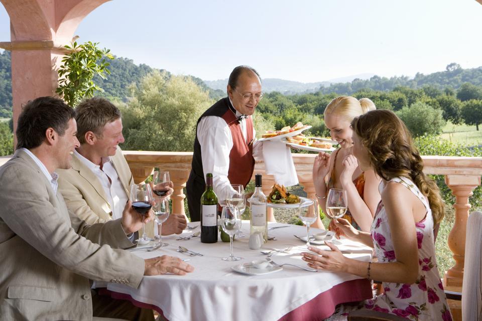 Serveur servant des repas à des couples bien habillés à la table sur le balcon du restaurant