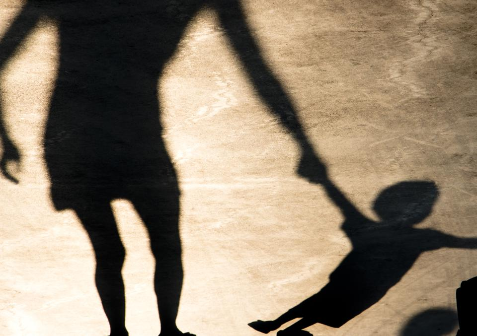 Shadows silhouettes of mother and child on summer promenade child tugging at mother