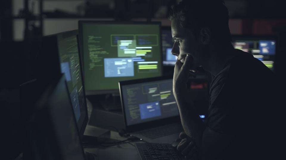 Computer developer working with computers at night