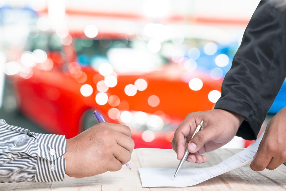Man signing car insurance document or lease paper.